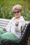 Starszy kobiety obsiadanie na ławce i zagraża z pięścią Fotografia Stock