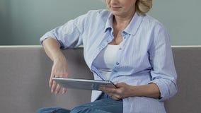 Starszy kobiety obsiadanie na leżance i scrolling ekranie pastylka, czytelniczy ebook zbiory