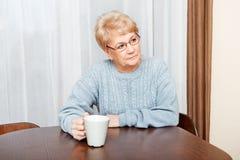 Starszy kobiety obsiadanie przy pić herbatą, biurkiem lub kawą i zdjęcia stock