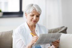 Starszy kobiety ocechowania ogłoszenie prasowe w domu obraz royalty free