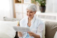 Starszy kobiety ocechowania ogłoszenie prasowe w domu fotografia royalty free