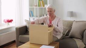 Starszy kobiety otwarcia pakuneczka pudełko w domu zbiory