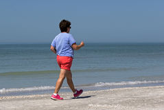 Starszy kobiety władzy odprowadzenie na plaży Zdjęcia Stock