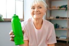 Starszy kobiety ćwiczenia opieki zdrowotnej mienia bidon w domu Obrazy Stock