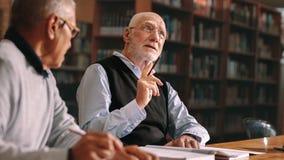 Starszy koledzy dyskutuje w szkole wyższej zdjęcia royalty free