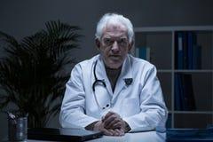 Starszy lekarz praktykujący w lekarki biurze Zdjęcia Royalty Free
