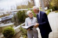 Starszy ludzie biznesu opowiada outdoors i dyskutuje documen zdjęcie stock