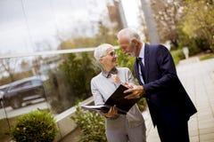 Starszy ludzie biznesu opowiada outdoors i dyskutuje documen obraz royalty free