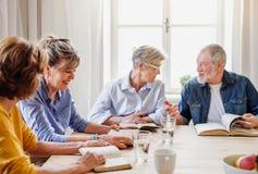 Starszy ludzie w biblii czytania grupie w domu kulturego klubie obrazy stock