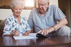Starszy mąż i żona robi papierkowej robocie wpólnie w domu zdjęcia royalty free