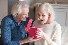 Starszy mąż przedstawia prezenta pudełko zdziwiona ukochana żona zdjęcie stock