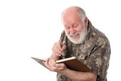 Starszy mężczyzna śmia się podczas gdy czytający książkę, odosobnioną na bielu Obrazy Royalty Free