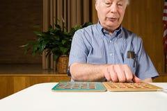Starszy mężczyzna bawić się bingo fotografia royalty free