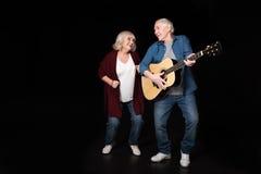 Starszy mężczyzna bawić się gitarę podczas gdy kobieta tanczy blisko Fotografia Royalty Free