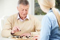 Starszy mężczyzna Bawić się warcabów Z Nastoletnią wnuczką Zdjęcie Royalty Free