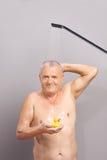 Starszy mężczyzna bierze prysznic i trzyma gumowej kaczki Obrazy Royalty Free