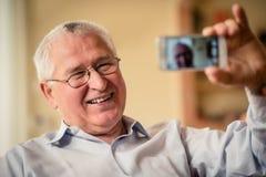 Starszy mężczyzna bierze selfie Zdjęcia Royalty Free