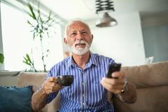 Starszy mężczyzna cieszy się oglądający tv w domu zdjęcie royalty free