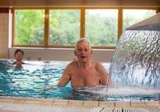 Starszy mężczyzna cieszy się prysznic w basenie fotografia stock