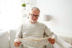 Starszy mężczyzna czyta gazetę w domu w szkłach Obraz Stock