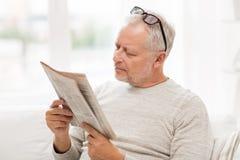 Starszy mężczyzna czyta gazetę w domu w szkłach Obrazy Royalty Free