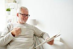 Starszy mężczyzna czyta gazetę w domu w szkłach Obrazy Stock