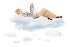 Starszy mężczyzna czyta lying on the beach na chmurach i książkę Zdjęcie Stock