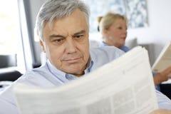 Starszy mężczyzna czyta nespaper z jego żoną beside w domu Fotografia Stock
