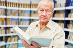 Starszy mężczyzna czyta wewnątrz książkę obraz stock
