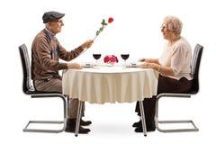 Starszy mężczyzna daje czerwieni róży starsza kobieta przy restauracyjnym stołem obrazy stock