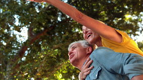 Starszy mężczyzna daje jego partnera piggyback na słonecznym dniu zbiory