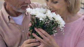 Starszy mężczyzna daje kwiat wiązce starzejąca się kobieta, szczęśliwa przechodzić na emeryturę para, rocznica zbiory