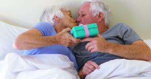 Starszy mężczyzna daje niespodzianka prezentowi kobieta na łóżku w sypialni zbiory wideo