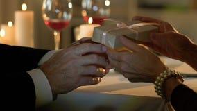 Starszy mężczyzna daje teraźniejszości kobieta na romantycznej dacie, małżeństwo rocznica zbiory