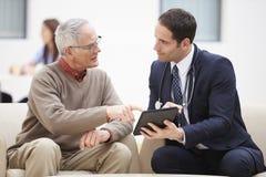 Starszy mężczyzna Dyskutuje rezultaty Z lekarką Na Cyfrowej pastylce Zdjęcia Stock