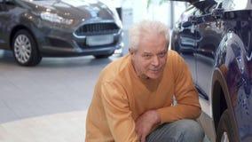Starszy mężczyzna egzamininuje samochodowego koło przy przedstawicielstwem handlowym zbiory