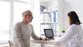 Starszy mężczyzna i lekarka z pastylka komputerem osobistym przy szpitalem 66 zbiory