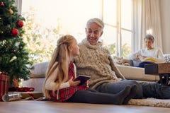 Starszy mężczyzna i wnuczka z cyfrową pastylką w domu Obrazy Stock