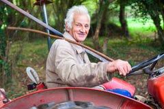 Starszy mężczyzna jedzie starego ciągnika w lesie zdjęcia royalty free
