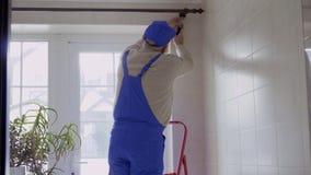 Starszy mężczyzna jest ubranym błękitnych ochronnych coveralls naprawia karnisz nad okno zdjęcie wideo