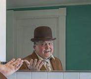 Starszy mężczyzna jest ubranym Derby ono podziwia w łazienki lustrze zdjęcia stock