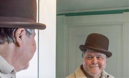 Starszy mężczyzna jest ubranym Derby w łazienki lustrze zdjęcie stock