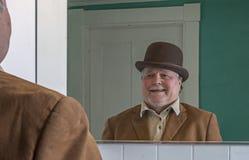 Starszy mężczyzna jest ubranym Derby w łazienki lustrze fotografia royalty free