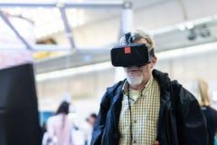 Starszy mężczyzna jest ubranym rzeczywistość wirtualna gogle ogląda rzeczywistości wirtualnej prezentację zdjęcia stock