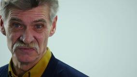 Starszy mężczyzna mówjący pokazuje różne emocje gdy zdjęcie wideo