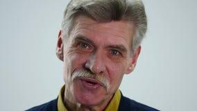 Starszy mężczyzna mówjący pokazuje różne emocje gdy zbiory
