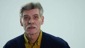 Starszy mężczyzna mówjący pokazuje różne emocje gdy zbiory wideo