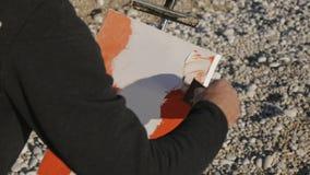 Starszy mężczyzna maluje obrazek na plaży Starszy męski artysta stosuje akrylową farbę kanwa z szeroką szpachelką przy zbiory