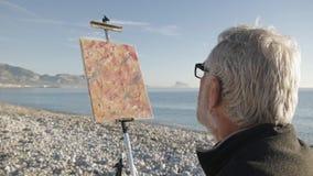 Starszy mężczyzna maluje obrazek na plaży Nad naramiennym widokiem starszy męski artysta patrzeje jego ostatnio malującego zbiory wideo