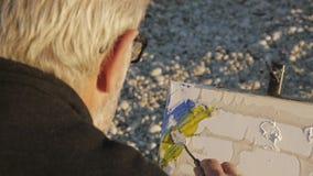 Starszy mężczyzna maluje obrazek na plaży Nad ramię strzałem starszy męski artysta stosuje żółtą farbę kanwa zbiory